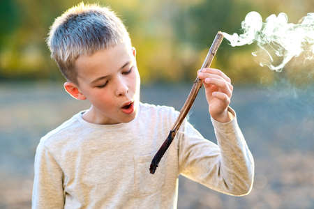 Child boy playing with smoking wooden stick outdoors. Standard-Bild