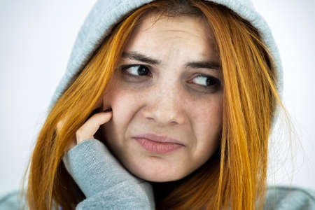Close up portrait of sad depressed young redhead woman wearing warm hoodie pullover.