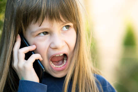 Portrait of angry child girl with long hair talking on cell phone. Little female kid having discussion on smartphone. Children communication concept. Standard-Bild