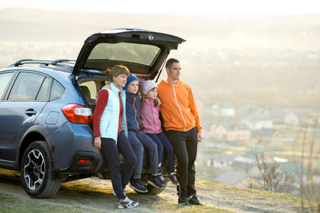 Happy family standing together near a car with open trunk enjoying view of rural landscape nature. Parents and their kids leaning on vehicle luggage compartment. Weekend travel and holidays concept.