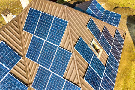 Aerial top view of new modern residential house cottage with blue shiny solar photo voltaic panels system on roof. Renewable ecological green energy production concept.