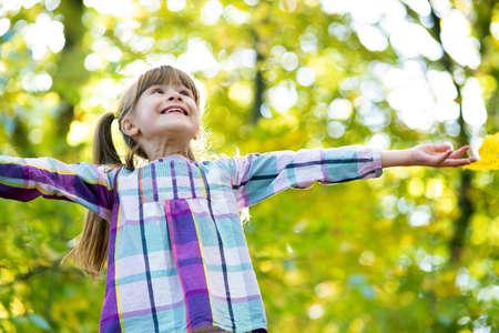 Portrait of happy pretty child girl having fun in autumn forest. Positive female kid enjoying warm day in fall park. Standard-Bild