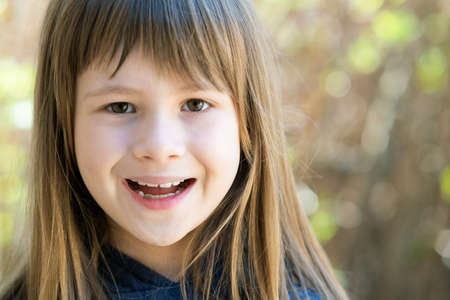 Portrait of pretty child girl with gray eyes and long fair hair smiling happily outdoors on blurred green bright background. Cute female kid on warm summer day outside. Standard-Bild