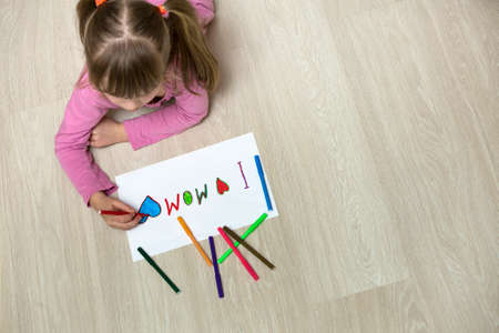 View from above of cute child girl drawing with colorful crayons I love Mom on white paper. Art education, creativity concept.