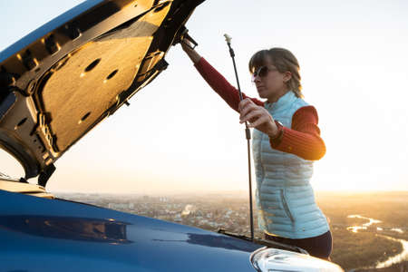 Young woman opening bonnet of broken down car having trouble with her vehicle. Female driver near auto with popped up hood. Stock Photo
