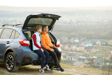 Happy couple standing together near a car with open trunk enjoying view of rural landscape nature. Man and woman leaning on family vehicle luggage compartment. Weekend travel and holidays concept.