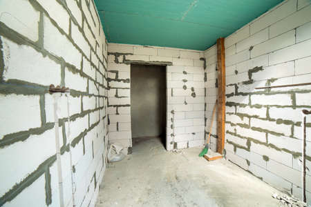 Interior of an apartment room with walls and ceiling under construction.