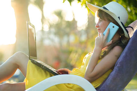Girl student in yellow summer dress resting on green lawn in summer park studying on computer laptop having conversation on mobile cell phone. Doing business and learning during quarantine concept.