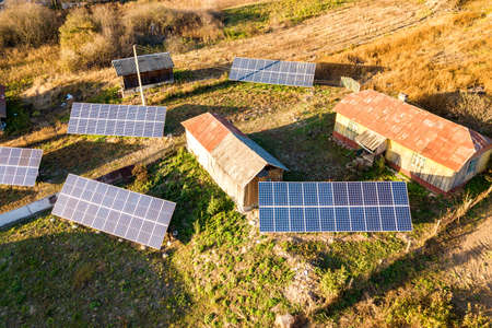 Aerial top down view of solar photo voltaic panels in green rural area. Clean renewable energy in private village environment.