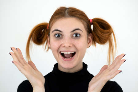 Closeup portrait of a funny redhead teenage girl with childish hairstyle smiling happily isolated on white backround.