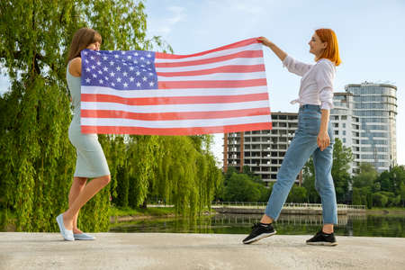 Two young friends women holding USA national flag in their hands standing together outdoors. Patriotic girls celebrating United States independence day.