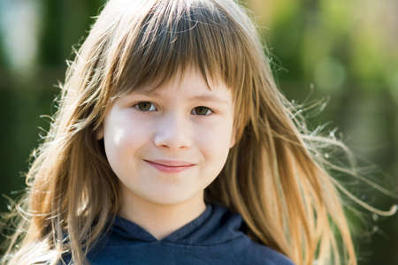Portrait of pretty child girl with gray eyes and long fair hair smiling outdoors on blurred bright background. Cute female kid on warm summer day outside.