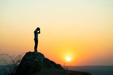 Silhouette of a woman hiker standing alone on big stone at sunset in mountains. Female tourist on high rock in evening nature. Tourism, traveling and healthy lifestyle concept.