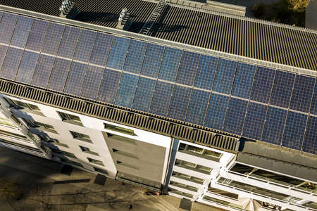 Aerial view of solar photovoltaic panels on a roof top of residential building block for producing clean electric energy. Autonomous housing concept. Banque d'images