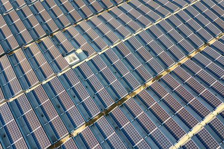 Aerial view of many photo voltaic solar panels mounted of industrial building roof. Banque d'images