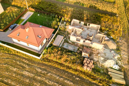 Top down aerial view of two private houses, one under construction with concrete foundament and brick walls and another finished with red tiled roof.