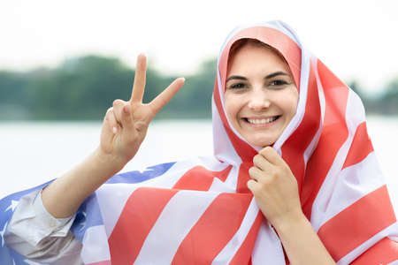 Portrait of young happy refugee woman with USA national flag on her head and shoulders. Positive muslim girl celebrating United States independence day. International day of democracy concept.
