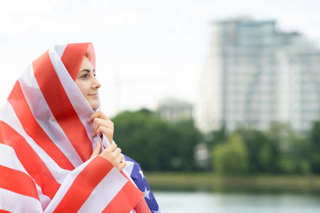 Young happy refugee woman with USA national flag on head and shoulders. Positive muslim girl traveling in United States. Banco de Imagens