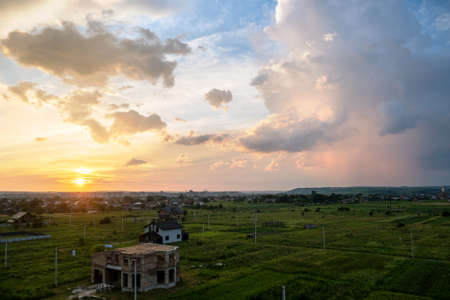 Dramatic sunset rural landscape with puffy clouds lit by orange setting sun and blue sky. Stock fotó - 151143409