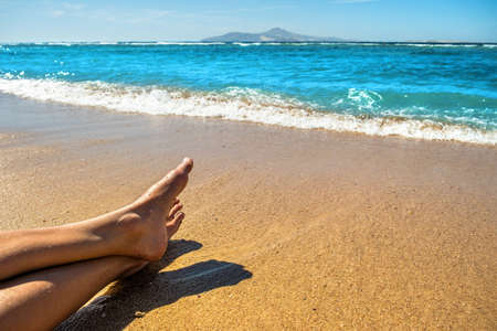 Long slim young woman legs relaxing lying down and sunbathing on sand tropical beach under hot sun in summer. Skincare, sun aging protection and sea travel concept.