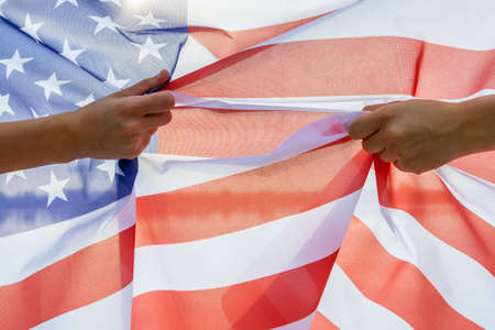 Two human hands holding USA national flag. Celebration of United States independence day concept.