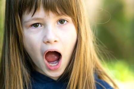 Portrait of surprised child girl outdoors in summer. Shocked female kid on a warm day outside.