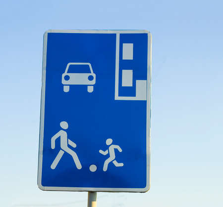 Information road sign, blue rectangular shield with human figures, car and parking marking. Attention, pedestrian zone recommendation.