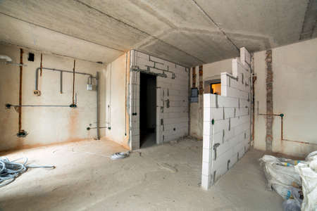 Interior of an apartment room with bare walls and ceiling under construction.
