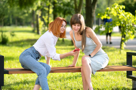 Two young girls friends sitting on a bench in summer park looking in red smartphone. Archivio Fotografico