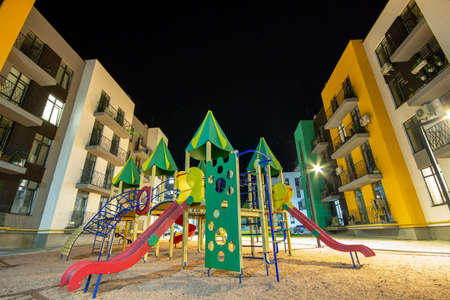 Children playground at night in residential district yard between apartment buildings. Stok Fotoğraf