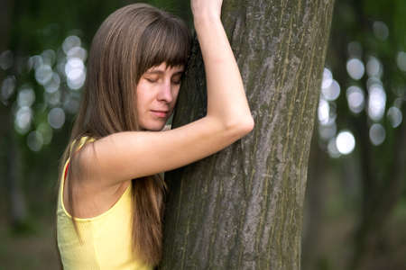 Young woman leaning to tree trunk in summer forest.