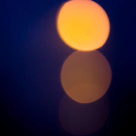 Bright orange round blurred moon or traffic lights on dark blue violet bokeh background.
