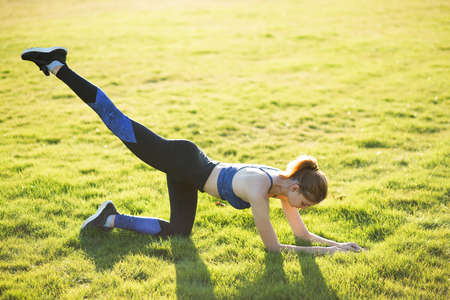 Young sportive woman doing fitness exercises on green grass in warm summer day outdoors.
