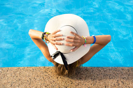Top view of young woman with long hair wearing yellow straw hat relaxing in warm summer swimming pool with blue water on a sunny day.
