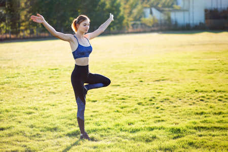 Young sportive woman doing yoga fitness exercises on warm summer day outdoors.