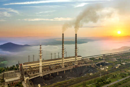 High power plant pipes with thick dirty smoke with wide valley with white fog and big lake between green mountains. Stock fotó