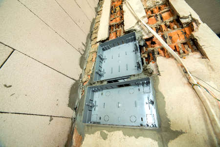 Electrical cables laid to plastic fusebox installed on the wall in a room under construction works. Banco de Imagens