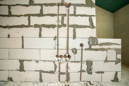 Deep grooves and holes in white brick wall made for installation of electrical cables. Stock fotó