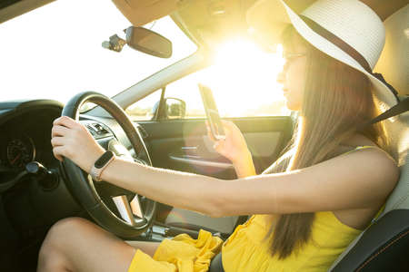 Young woman driver in yellow summer dress using mobile phone behind steering wheel driving a car.