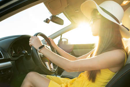 Young woman driver in summer yellow dress and straw hat driving a car.