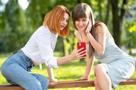 Two young girls friends sitting on a bench in summer park looking in red smartphone. Foto de archivo