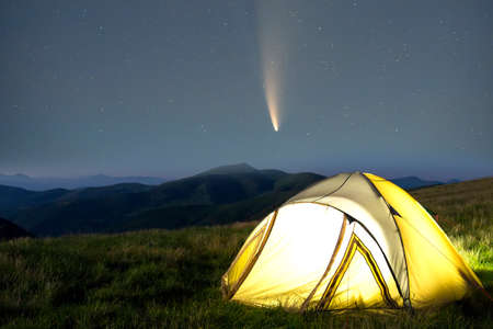Tourist hikers tent in mountains at night with stars and Neowise comet with light tail in dark night sky.