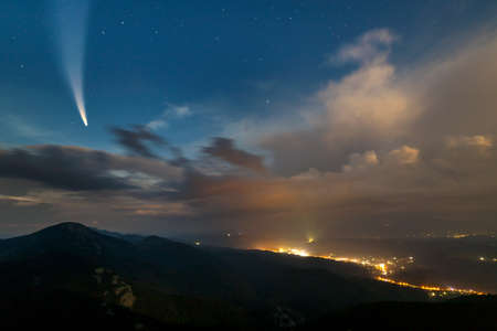 Summer night in mountains with starry dark blue cloudy sky and Neowise comet with light tail. 스톡 콘텐츠