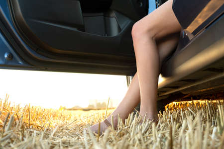 Bare legs of a female driver standing near her car in summer field.