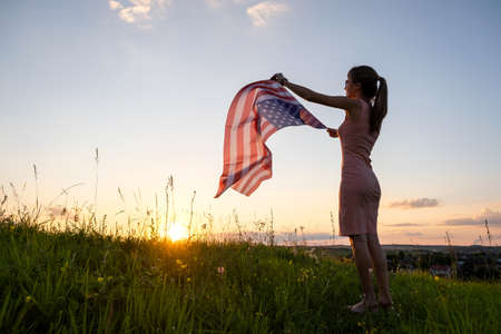 Back view of happy young woman posing with USA national flag outdoors at sunset. Positive girl celebrating United States independence day. International day of democracy concept. 스톡 콘텐츠