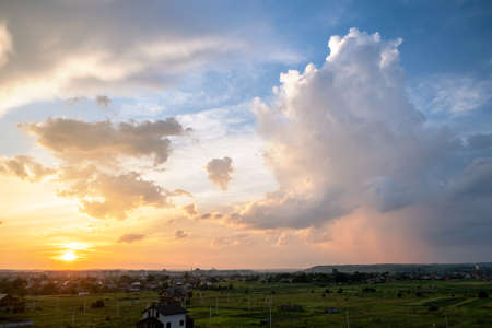 Dramatic sunset landscape of rural area with stormy puffy clouds lit by orange setting sun and blue sky. 스톡 콘텐츠