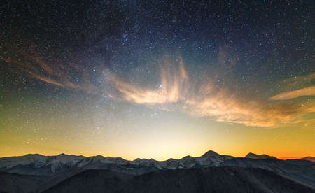 Amazing night mountain landscape with high peaks and bright starry sky above.