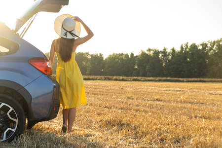 A girl driver in yellow summer dress and straw hat standing near a car enjoying warm summer day at sunrise. Travel and vacation concept. 스톡 콘텐츠