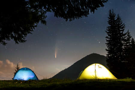 Two brightly lit tourist tents on forest clearing in mountains with starry sky and Neowise comet with light tail.