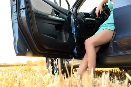 Bare legs of a woman driver standing near her car in summer field. Foto de archivo